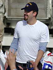 Smiling young man with a trim goatee and moustache, wearing a white t-shirt and a baseball cap. He is surrounding by hands reaching out to him.