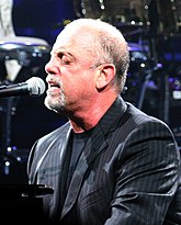 A man with a goatee and his eyes closed behind a microphone on a piano, wearing a black shirt and striped jacket.