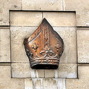 Photograph of a bishop's mitre set in a wall.