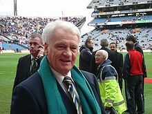 An elderly man in a shirt and tie, wearing a green scarf, standing by a football pitch, smiling
