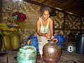 Brao woman making rice wine in a jar.JPG