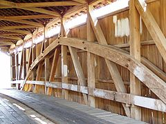 Interior structure of a covered bridge utilizing a kingpost with a Burr Arch structure