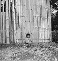 COLLECTIE TROPENMUSEUM Peuter zittend tegen een bamboe afscheiding TMnr 20000159.jpg