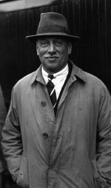 A casual outdoor photo of C. H. Douglas. He is a suntanned man with a white moustache and shrewd smile. He wears a fedora and grubby old gabardine coat.