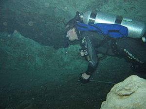 Cave diving - A cave diver running a reel with guide line into the overhead environment