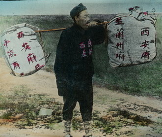 """Mail bag - China, country postman, circa 1900, carrying a yoke with large """"mail bags""""."""