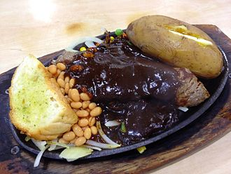 Mixed grill - Chinese style mixed grill consisting of lamb chops, chicken chops, beef steak, baked potato, baked beans and garlic toast topped with black pepper sauce.