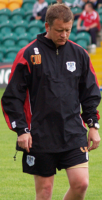 A man is looking down at the ground while walking, wearing a tracksuit top and shorts