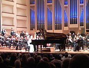 Performance of a piano concerto involves a piano on stage with the orchestra