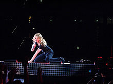 A female blond performer sitting on all fours on a stage. She is singing to a microphone while holding it with her right hand. The background is dark but a red glow falls on the woman.