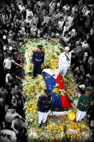 Death and funeral of Corazon Aquino - Aquino's flag-draped casket borne on a flatbed truck during the funeral procession. This was intentionally modelled after the funeral of her husband, Benigno, a quarter century before.