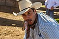 Cowboy with testicles of neutered calf in his mouth (31999083823).jpg