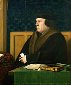 A Tudor man in a large coat and hat, possibly of fur, sitting at a desk