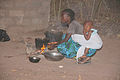 Crouching girl with child on her back Gambia.jpg