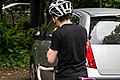 Cyclist putting on helmet for cycling on road.jpg