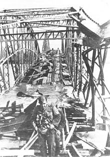 a black and white photograph looking along a damaged steel girder bridge from one end