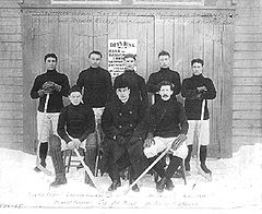 "Seven men in hockey uniforms are arranged in two rows in front of a large door, on which are the words ""Dey's Rink"" In the middle of the front row, is their manager, wearing a dark coat and bowler hat."