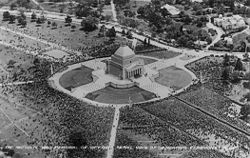 Aerial view of a square temple structure, surrounded by thousands of people.
