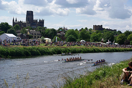 Durham Cathedral and castle as seen from the river bank whilst a boat race takes place between University College, Durham and Newcastle University Durham regatta Univ College Durham v's Newcastle Uni.jpg