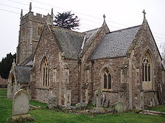 Stone building with square tower and arched windows.