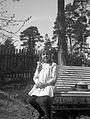 En flicka sitter på en trädgårdsbänk.I bakgrunden ett staket - Nordiska Museet - NMA.0057512.jpg