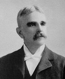 A man with graying hair and a mustache wearing a black jacket and vest and white shirt and bowtie