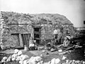 Evicted family outside thatched stone cottage with their belongings, Derrybeg.jpg