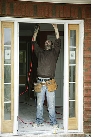 Handyman - A handyman working on a door frame