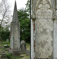 A granite funerary monument in the shape of a spire among other headstones
