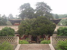 A Chinese temple building. It is built on a raised terrace and two trees nearly obscure the building from view.