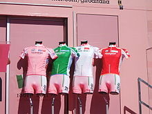 Four cycling jerseys – pink, green, white, and red, from left to right – are arranged on mannequin torsos in front of a pink wall.