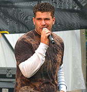 A man with dark curly hair singing into a microphone