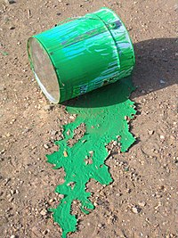 Paint can with spilled green paint on ground