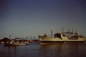 HMAS Supply being towed along the Brisbane river in late 1967