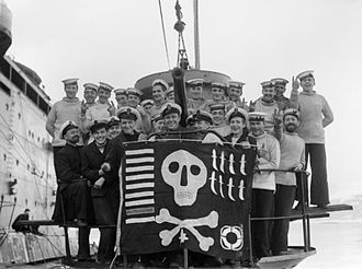 "Skull and crossbones (military) - 6 February 1942 Members of the crew of HMS Utmost with their ""Jolly Roger"" success flag, photographed alongside submarine depot ship HMS FORTH in Holy Loch, on their return from a year's service in the Mediterranean"