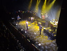 Pop group performing on stage, spotlit, with row of darkened fans in the foreground