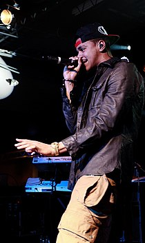 A man wearing a cap and a black leather jacket raps into a microphone.
