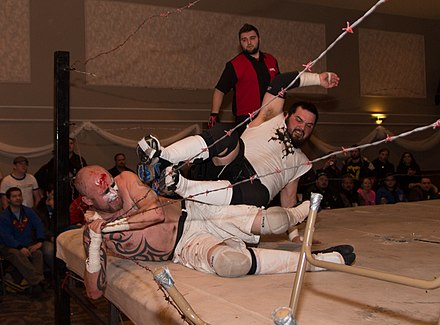 Joey Kings (in white top, right) dropkicks Warhed into the barbed wire ropes Joey Kings dropkick.jpg