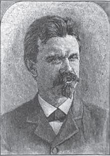 A man with thick, dark hair, a mustache and a goatee, wearing a white shirt and dark jacket