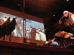 جان ویلیامز در حال رهبری موسیقی متن فیلم مهاجمان صندوق گمشده در تالار آوری فیش
