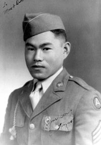 "Head and shoulders of a young man wearing a garrison cap and a military jacket with three chevrons on the upper left sleeve and a whistle hanging from a chain attached to his right shoulder. In the top left corner of the photo is written ""To Mom & Dad"" and in the lower right ""your son! Kazuo""."