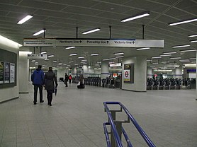 a large white tiled space with a range of ticket barriers in the distance, overhead signs provide directions towards Underground lines