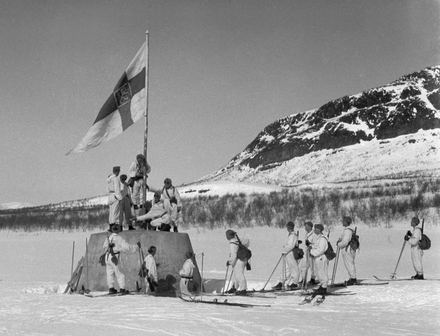 Finnish soldiers raise the flag at the three-country cairn between Norway, Sweden and Finland on 27 April 1945 after the end of the Lapland War and thus, the end of World War II in Finland Kolmen valtakunnan rajapyykki 27.4.1945.png