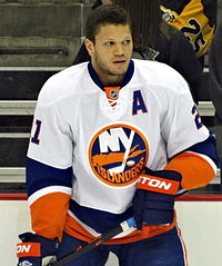 Kyle Okposo standing on the ice with his hockey stick and no helmet on.