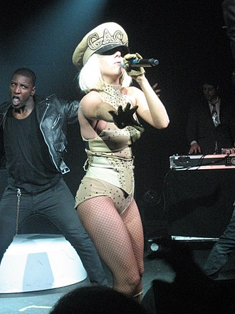 "Poker Face (Lady Gaga song) - Gaga wearing a yellow leotard and an admiral's cap, performing ""Poker Face"" on The Fame Ball Tour"
