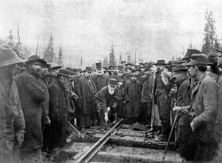 Lord Strathcona drives the Last Spike of the Canadian Pacific Railway, at Craigellachie, November 7, 1885. Completion of the transcontinental railroad was a condition of entry into Confederation. LastSpike Craigellachie BC Canada.jpg