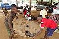 Lavage d'un réservoir d'essence de voiture entre un apprenti aidé par une fille dans un garage mécanique auto à Zê au Bénin.jpg