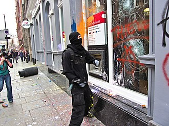 2011 London anti-cuts protest - A protester smashing the window of a branch of the HSBC bank in Cambridge Circus, London