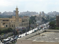 A mosque and a church in Suez Canal Street, Al Shatby. The Alexandria Tram line is visible crossing the street.