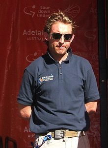 A blond man in his late thirties wearing a dark blue polo shirt and sunglasses, with his hands behind his back such that no part of his arms below either elbow is visible.